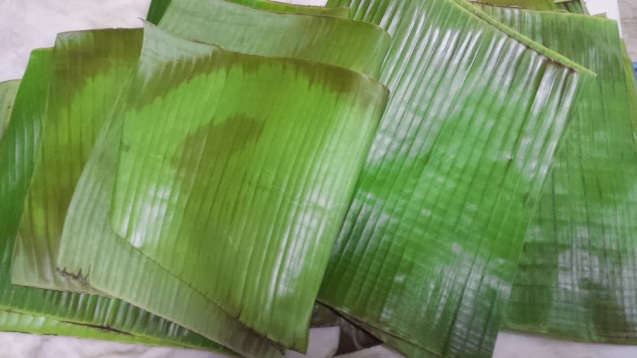 While cooling the rice mixture, heat the banana leaves over the fire to soften